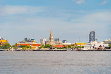Temple of Dawn or Wat Arun with reflection of Chao Phraya River, Bangkok, Thailand in Rattanakosin Island in architecture, Urban old town city, skyline. downtown area at noon with blue sky.