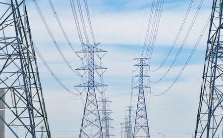 High voltage poles. Power lines on utility tower and cable wires in energy electric technology, network, and industry concept. Generator pylon. Transmission and substation. Banco de Imagens