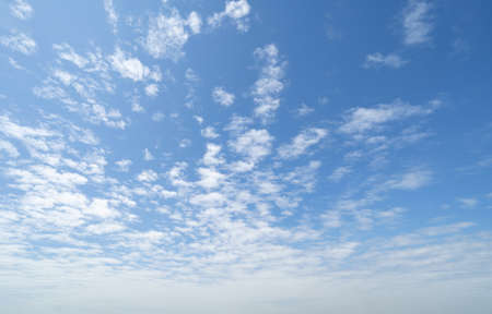Clear blue sky with white fluffy clouds at noon. Day time. Abstract nature landscape background. Banco de Imagens