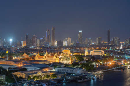 Temple of the Emerald Buddha, Grand palace, Temple of Dawn, Bangkok City, Thailand. Wat Phra Kaew, and Chao Phraya River, skyscraper buildings. Downtown skyline. Buddhist temples at night. Editorial
