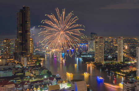 Happy New Year Fireworks Festival Event at Taksin bridge with Chao Phraya River in Bangkok, Thailand. Financial district and skyscraper buildings. Downtown skyline at night. Banco de Imagens