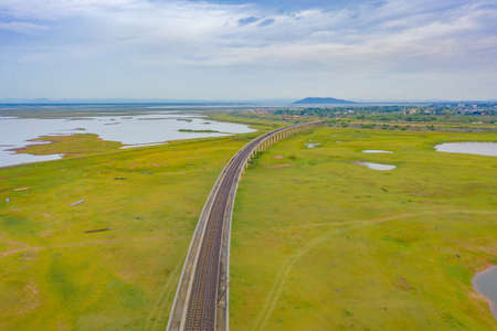 Aerial view of Thai local train on railway bridge at Pa Sak Jolasid Dam, the biggest reservoir in central Thailand, in Lopburi province with cloudy sky in transportation and travel concept. Banco de Imagens - 158319167