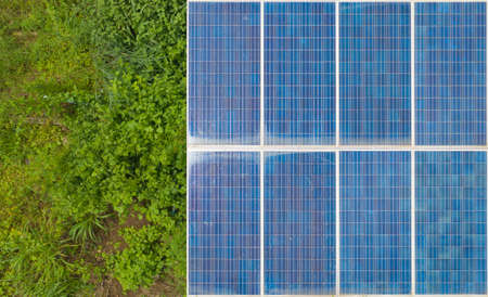 Aerial view of solar panels or solar cells on the roof in farm. Power plant with green field, renewable energy source in Thailand. Eco technology for electric power in industry.