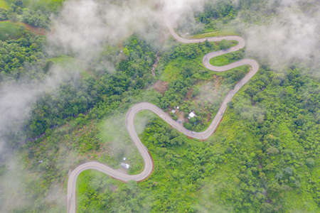Aerial view of cars driving on curved, zigzag curve road or street on mountain hill with green natural forest trees in rural area of Phu Tub Berk, Phetchabun, Thailand.