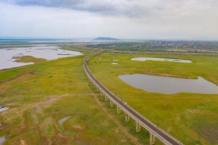 Aerial view of Thai local train on railway bridge at Pa Sak Jolasid Dam, the biggest reservoir in central Thailand, in Lopburi province with cloudy sky in transportation and travel concept. Banco de Imagens