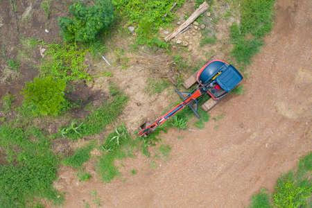 Aerial view of Construction tractor car, bulldozer, or backhoe digging road or street in transportation and agriculture concept. Engine working in grass farm field and land. Banco de Imagens
