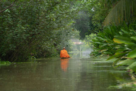 Local Thai monks with alms. A man sailing wooden boat in canal or river for receiving food, Traditional Thai Buddhism lifestyle. Asia, Thailand. Banco de Imagens