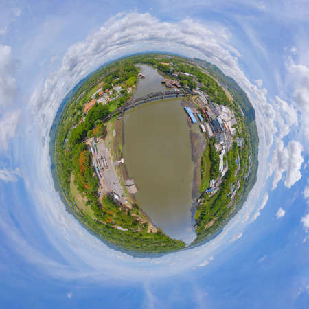 Little planet 360 degree sphere. Panorama of aerial view of River Kwai Bridge with train rail way with Chao Phraya River, Tha Ma Kham, Mueang Kanchanaburi District, Thailand.