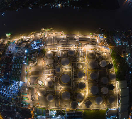Aerial view of petrochemical oil refinery and sea in industrial engineering concept in Bangna district at night, Bangkok City, Thailand. Oil and gas tanks pipelines in industry. Modern metal factory.