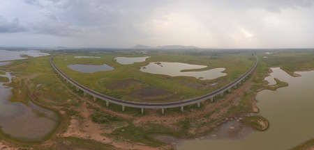 Aerial view of Thai local train on railway bridge at Pa Sak Jolasid Dam, the biggest reservoir in central Thailand, in Lopburi province with cloudy sky in transportation and travel concept. Imagens