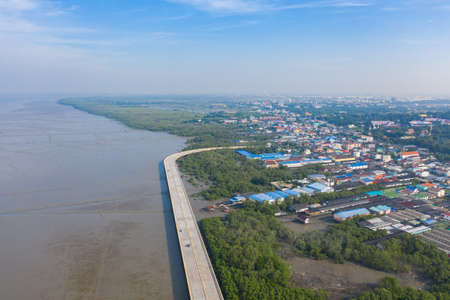 Aerial view of Chon Ra Mak Vi Tee Bridge Road in Sri Racha district with sea, Chonburi skyline, Thailand. Urban city in Asia. Architecture landscape background.