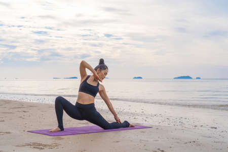 An Asian woman in yoga class club doing exercise and yoga at natural beach and sea coast outdoor in sport and recreation concept. People lifestyle activity. Banco de Imagens - 160854629