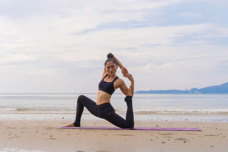 An Asian woman in yoga class club doing exercise and yoga at natural beach and sea coast outdoor in sport and recreation concept. People lifestyle activity. Banco de Imagens - 160854630