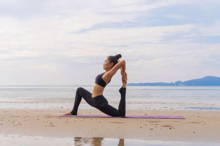 An Asian woman in yoga class club doing exercise and yoga at natural beach and sea coast outdoor in sport and recreation concept. People lifestyle activity. Banco de Imagens - 160854631