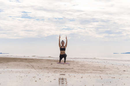 An Asian woman in yoga class club doing exercise and yoga at natural beach and sea coast outdoor in sport and recreation concept. People lifestyle activity. Banco de Imagens