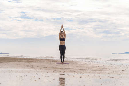 An Asian woman in yoga class club doing exercise and yoga at natural beach and sea coast outdoor in sport and recreation concept. People lifestyle activity. Banco de Imagens - 160854636