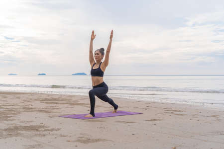 An Asian woman in yoga class club doing exercise and yoga at natural beach and sea coast outdoor in sport and recreation concept. People lifestyle activity. Banco de Imagens - 160854639