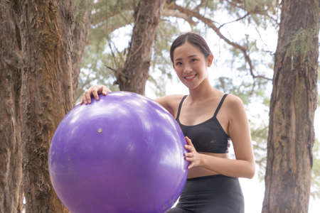 Portrait of an Asian woman holding a ball in yoga class club doing exercise and yoga at natural beach and sand outdoor in sport and recreation concept. People lifestyle activity.