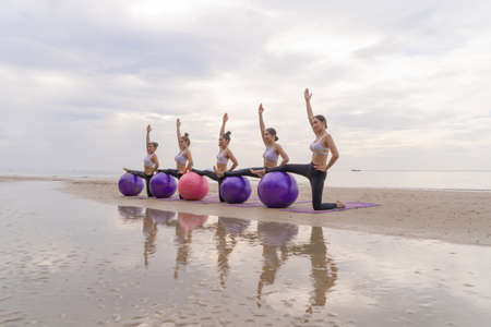 Group of Asian women in yoga class club doing exercise and yoga at natural beach and sea coast outdoor in sport and recreation concept. People lifestyle activity.