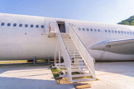 Passenger stair with boarding ramp steps. Commercial airplane, aircraft with blue sky background in travel trip and transportation concept. Flying vehicle.