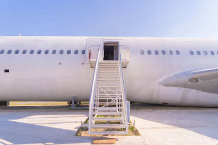 Passenger stair with boarding ramp steps. Commercial airplane, aircraft with blue sky background in travel trip and transportation concept. Flying vehicle. Banco de Imagens - 160981951