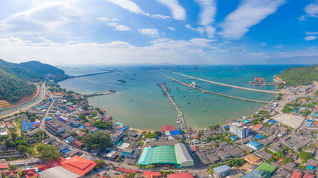 Aerial view of pier with boats with container cargo ship in the export and import business and logistics international goods in ocean sea. Shipping to the harbour by crane in Pattaya harbour, Thailand