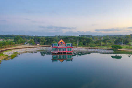 Aerial view of home, house or resort under contruction with lake or river with reflection. Green mountain hill. Nature landscape background in Khao Yai, Nakhon Ratchasima, Thailand. Bungalow Banco de Imagens