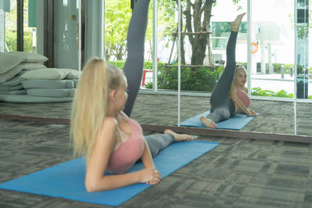 Portrait of fit white healthy woman, caucasian person stretching, doing exercise and yoga, working out, and training in gym or fitness center in sport and recreation concept. Lifestyle activity. Banco de Imagens - 161324677
