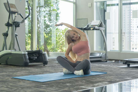 Portrait of fit white healthy woman, caucasian person stretching, doing exercise and yoga, working out, and training in gym or fitness center in sport and recreation concept. Lifestyle activity. Banco de Imagens - 161324678