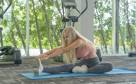 Portrait of fit white healthy woman, caucasian person stretching, doing exercise and yoga, working out, and training in gym or fitness center in sport and recreation concept. Lifestyle activity. Banco de Imagens - 161324682