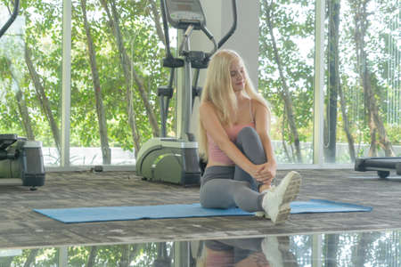 Portrait of fit white healthy woman, caucasian person stretching, doing exercise and yoga, working out, and training in gym or fitness center in sport and recreation concept. Lifestyle activity. Banco de Imagens - 161324686