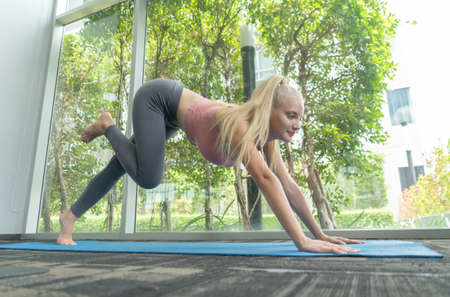Portrait of fit white healthy woman, caucasian person stretching, doing exercise and yoga, working out, and training in gym or fitness center in sport and recreation concept. Lifestyle activity. Banco de Imagens