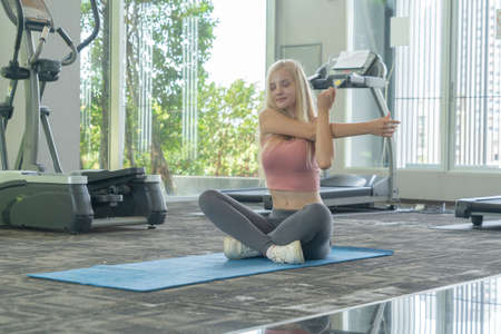 Portrait of fit white healthy woman, caucasian person stretching, doing exercise and yoga, working out, and training in gym or fitness center in sport and recreation concept. Lifestyle activity. Banco de Imagens - 161324688
