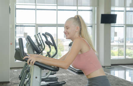Portrait of fit white healthy woman, caucasian person, doing exercise, working out, and training in gym or fitness center in sport and recreation concept. Lifestyle activity.