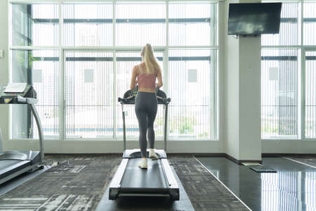 Portrait of fit white healthy woman, caucasian person, running or jogging on treadmill, and training in gym or fitness center in sport and recreation concept. Lifestyle activity. Banco de Imagens - 161324743