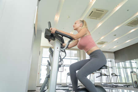 Portrait of fit white healthy woman, caucasian person, doing exercise, working out, and training in gym or fitness center in sport and recreation concept. Lifestyle activity. Banco de Imagens - 161324745