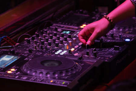 DJ plays and mixes on CD players or track at nightclub during party. Nightlife of disco club in disco pub club bar background for party music dancing festival performance. Entertainment nightlife.