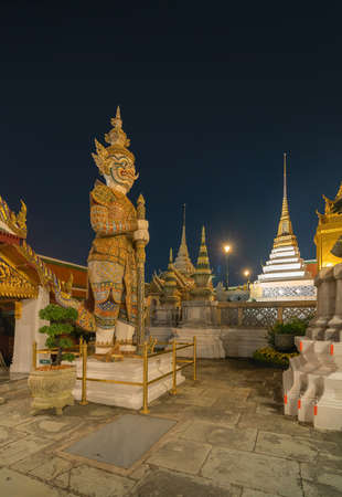 Giant guardian statue of Golden pagoda at Temple of the Emerald Buddha in Bangkok, Thailand. Wat Phra Kaew and Grand palace in old town, urban city. Buddhist temple, Thai architecture at night.