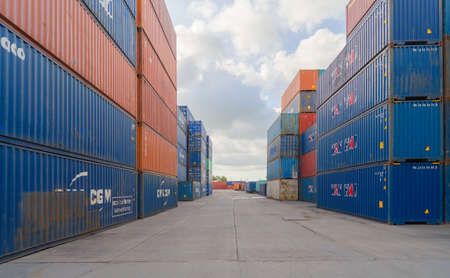 Shipping container site loading by crane in logistic port warehouse storage factory manufacturing business transportation import and export goods of freight business carrier.