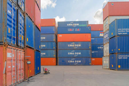 Shipping container site loading by crane in logistic port warehouse storage factory manufacturing business transportation import and export goods of freight business carrier. Banco de Imagens - 163430946