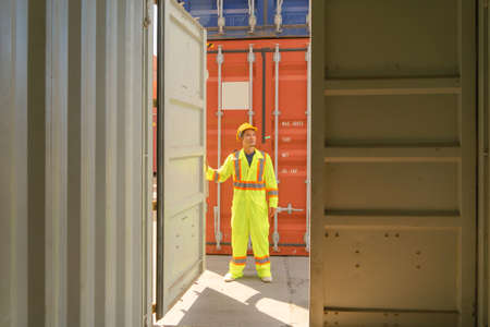 Asian logistic worker engineer man working in cargo container warehouse industry factory site in export, import, and transportation concept. Business people lifestyle. Distribution service.