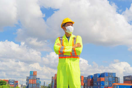 Sick Asian logistic worker engineer man working in cargo container,wearing a face mask in warehouse industry factory site. Export, import concept. Business people.  virus and health care concept