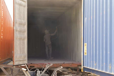 Industrial worker spray to clean inside container storage logistic shipping freight business manufacturing. Warehouse store.