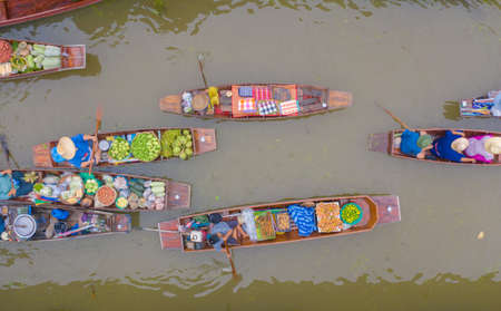 Damnoen Saduak Floating Market or Amphawa. Local people sell fruits, traditional food on boats in canal, Ratchaburi District, Thailand. Famous Asian tourist attraction destination. Festival in Asia.