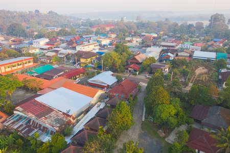 Aerial view of roofs of local village houses. Residential buildings in Ubon Ratchathani, Thailand. Urban city town in Asia. Architecture landscape background. Top view. Rural area.