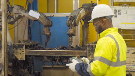 Black African American man, an engineer or worker control the smart robot welding hand system automated manufacturing machine engine in factory, industry equipment in operation warehouse. People.