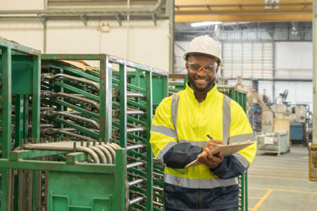 Portrait of Black African American man, an engineer or worker, with safety outfit checking quality control of product, car seat manufacturing factory industry plant in warehouse store. People.