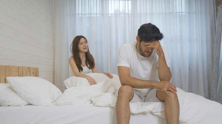 Frustrated angry Asian girlfriend dissatisfy or fight with her boyfriend, young couple in relationship problem on bed in bedroom at home. People lifestyle. Marriage trouble. Multi ethnic. Stock Photo
