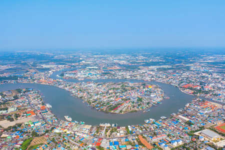 Aerial view of buildings with curve of Chao Phraya River. Samut Sakhon skyline near Bangkok, Urban city in downtown area at noon, Thailand.