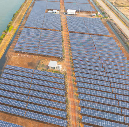 Aerial view of solar panels or solar cells on the roof in farm. Power plant with lake or river, renewable energy source in Thailand. Eco technology for electric power in industry. Photovoltaic cells